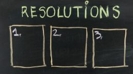 list of resolutions on blackboard with three blank, numbered sticky